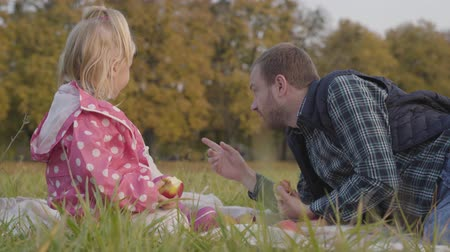 apple park : Little girl in dotted pink jacket and adult caucasian man sitting on the meadow and eating apples. Father spending autumn day with his lovely daughter outdoors. Stock Footage