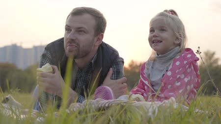 пунктирный : Portrait of caucasian father and his little blonde daughter sitting on the meadow and eating apples. Little girl in dotted pink jacket and adult caucasian man spending autumn day together outdoors. Стоковые видеозаписи