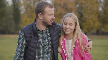 defender : Smiling caucasian man approaching to the young blonde girl on the foreground and hugging her. Father making piece with his teen daughter dressed in pink jacket in the autumn park.