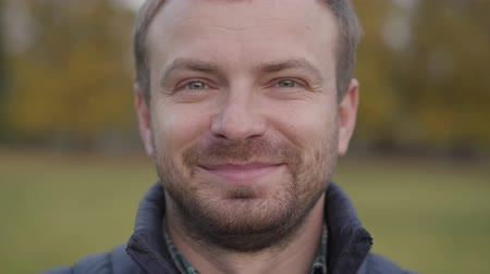 satysfakcja : Close-up face of an adult caucasian man looking at the camera and making faces. Bearded guy with grey hair and grey eyes standing on the autumn meadow and smiling.