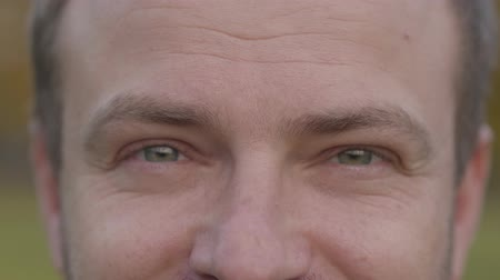 rendes : Extreme close-up of an adult caucasian mans grey eyes. Grey-haired guy looking at the camera and making faces.