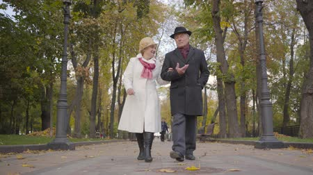 senior lifestyle : Senior Caucasian couple walking in the autumn park. Mature woman in white coat talking to her lovely husband and smiling.
