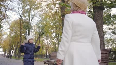 sikátorban : Little Caucasian girl in white hat and warm blue coat jumping in front of her grandmother walking along the alley. Mature woman in beige cloche hat and white coat spending time with her granddaughter Stock mozgókép