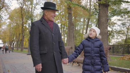moudrý : Senior Caucasian man in elegant black hat and coat strolling with his granddaughter along the alley in the autumn park. Little cute child talking with her wise grandfather and smiling.