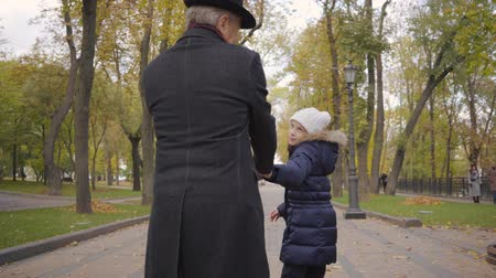 moudrý : Back view of a mature Caucasian man in elegant black hat and coat strolling with his granddaughter along the alley in the autumn park. Pretty cheerful child running away from her grandfather.