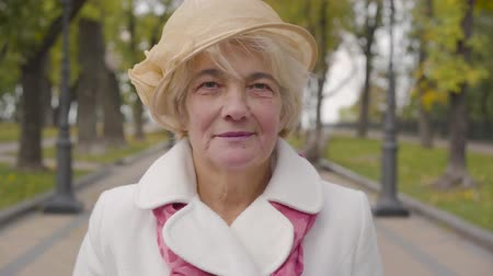 bege : Close-up of senior Caucasian woman with blue eyes looking at the camera and smiling. Mature lady in beige cloche hat standing in the autumn park. Vídeos