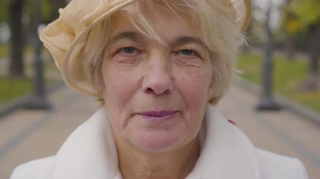 moudrý : Extreme close-up of senior Caucasian woman with blue eyes looking at the camera. Mature lady in beige cloche hat standing in the autumn park.