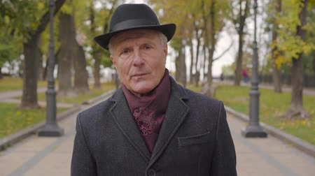 avelã : Close-up of a senior Caucasian man with hazel eyes dressed in elegant black hat and coat looking at the camera. Mature guy standing in the autumn park.