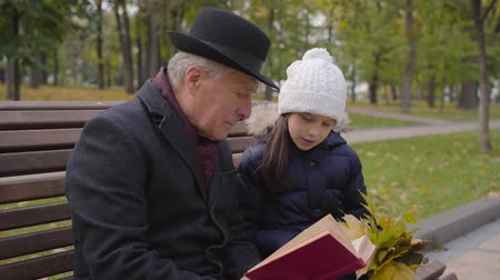 moudrý : Mature Caucasian man in classic clothes sitting on the bench with his granddaughter and reading a book in red cover. Pretty smiling girl listening to her wise grandfather attentively.