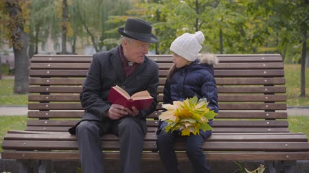 moudrý : Portrait of a mature Caucasian man in classic clothes sitting on the bench with his granddaughter and reading a book. Smiling girl holding a buch of yellow leaves and listening to her grandfather .