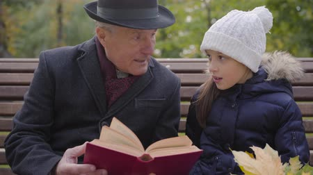 moudrý : Close-up portrait of a mature Caucasian man in classic clothes sitting on the bench with his granddaughter and reading a book in red cover. Pretty smiling girl listening to her wise grandfather.
