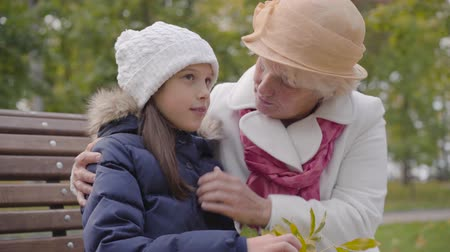 moudrý : Senior Caucasian woman in beige cloche hat and white coat fixing the white hat of her granddaughter. Happy grandmother sitting with young pretty girl on the bench in the autumn park.