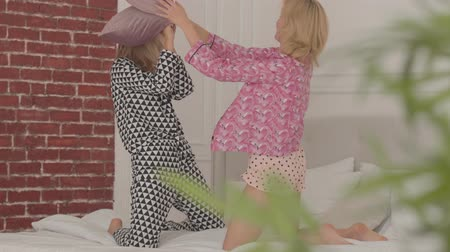 pajama : Two laughing blonde Caucasian friends fighting with pillows at the white bed. Beautiful girls having pajama party in the bedroom at home.
