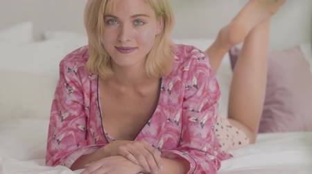 pajama : Young blonde Caucasian girl with grey eyes dressed in pink pajama laying on the white soft bed and looking at the camera. Happy smiling woman resting at home. Stock Footage