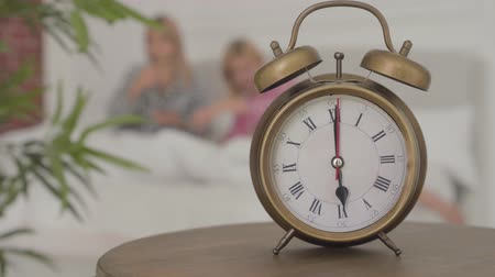 camisola : Close-up of an old-fashioned alarm clock showing 6 pm with two blonde Caucasian women going to bed behind it. Girls resting after the pajama party at home. Vídeos