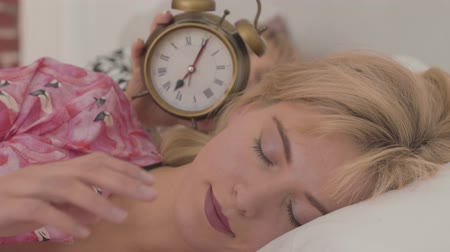 camisola : Close-up face of a beautiful blonde Caucasian woman sleeping and her friend approaching alarm clock showing 6 am from the background. Cute grey-eyed girl waking up at home.