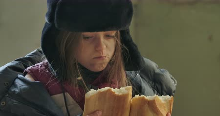 greedily : Close-up portrait of a homeless girl in hat with earflaps greedily eating the loaf of bread. Hungry refugee living on the streets.