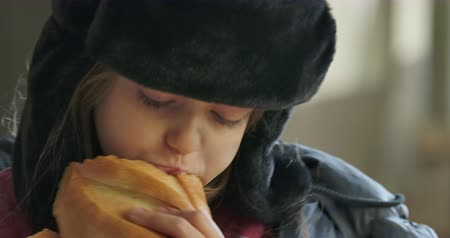 greedily : Close-up portrait of a homeless girl with grey eyes in hat with earflaps greedily eating the loaf of bread. Hungry refugee living on the streets.