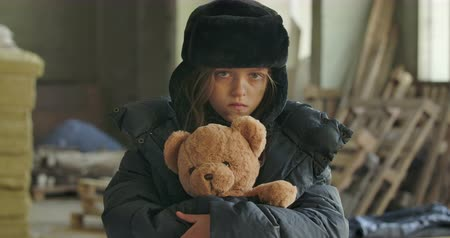 abraço : Portrait of a homeless girl with grey eyes wearing hat with earflaps looking at the camera and hugging mudtard teddy bear. Hopeless refugee living on the streets.