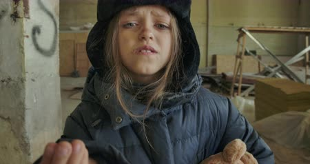 refugee crisis : Little Syrian refugee in dirty winter clothes asking for a handout. Hungry homeless girl with beautiful grey eyes living on the streets.