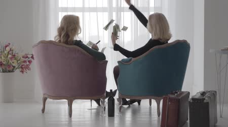 cigar : Back view of rich Caucasian women sitting in comfortable armchairs and scaterring money. Senior ladies spending vacations with a bottle of wine and cigars. Slow motion. Stock Footage