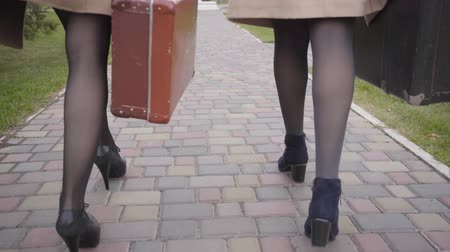 rajstopy : Close-up of legs in high heels of two women taking old travel bags and walking away. Elegant female friends travelling together.