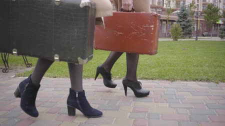 punčocháče : Side view of legs in high heels of two women holding old travel bags and walking. Elegant female friends travelling together.