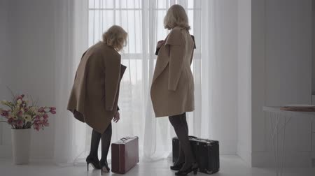 érettség : Two senior blonde Caucasian women in elegant beige coats walking with travel bags to the window. Rich senior businessladies talking to each other and smiling. Stock mozgókép