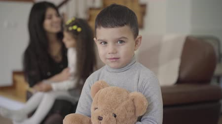 ursinho de pelúcia : Smiling Middle Eastern boy with grey eyes and dark hair holding the teddy bear and looking at the camera. Child posing at home while his sister and mom playing at the background.