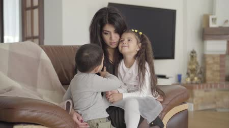 avelã : Beautiful Middle Eastern woman sitting on the armchair and talking to her two little children. Happy mother spending weekends with her lovely son and daughter at home. Stock Footage