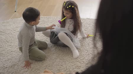 apito : Two little Middle Eastern children playing with party whistles and taking them away from each other. Cute siblings spending free time together at home.