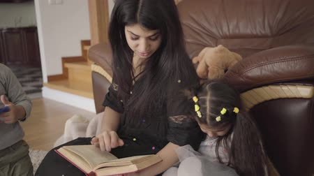 elâ : Pretty Middle Eastern woman reading the book to little children. Mother educating her lovely son and daughter at home. Stok Video