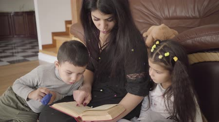 avelã : Charming Middle Eastern woman reading the book to little children. Mother educating her lovely son and daughter at home. Stock Footage