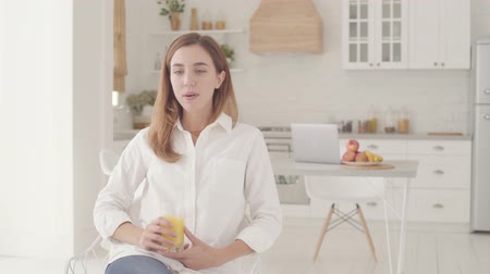 jus d orange : Young beautiful Caucasian woman sitting in light modern kitchen drinking orange juice and going to the background to laptop. Pretty smiling girl spending weekends at home.