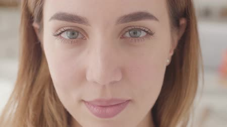 неформальный : Extreme close-up of a beautiful Caucasian woman with grey eyes looking at the camera and smiling.
