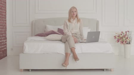 remotely : Portrait of a blond Caucasian businesswoman with grey eyes sitting with laptop on the bed and thinking. Young beautiful lady in official clothes working online from home. Stock Footage