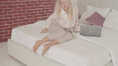 remotely : Confident blond Caucasian businesswoman taking off high heels sitting on the bed at home. Young exhausted lady in official clothes working online from home. Stock Footage