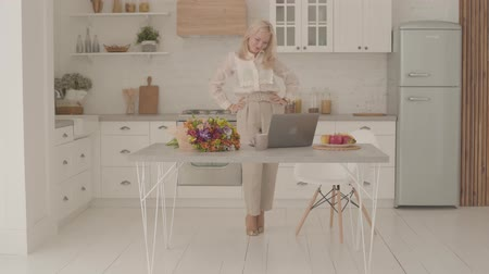 news stand : Happy Caucasian lady with blond hair standing in the modern kitchen, looking at laptop and making victory gesture. Adult woman in official clothes starting getting good news online.