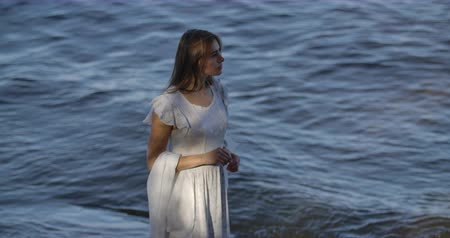 düşünürken : Sad brunette Caucasian woman in light white dress standing on the background of sea waves and thinking. Attractive girl spending summer evening on the beach.