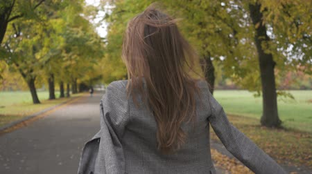 verhuizen : Close-up of a slim Caucasian woman in checkered jacket and mustard dress turning around and strolling along the road. Beautiful brunette girl walking in the autumn park.