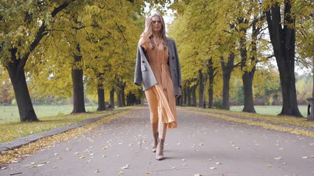 crows feet : Charming Caucasian brunette girl in mustard dress and checkered jacket walking along the road covered with yellow leaves. Pretty brunette woman strolling in the autumn park. Stock Footage