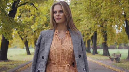 crows feet : Close-up of a confident Caucasian girl in mustard dress and checkered jacket walking along the road. Pretty brunette woman strolling in the autumn park on weekends.