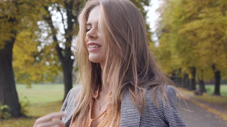 crows feet : Smiling Caucasian girl putting on checkered jacket and looking away. Nice brunette woman in mustard dress with tweed print standing in the autumn park.