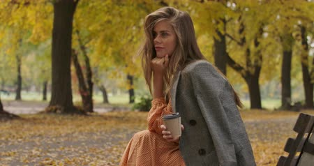 musztarda : Side view of charming Caucasian woman with long brown hair and green eyes sitting on the bench in the autumn park. Attractive girl holding a cup of coffee and smiling. Cinema 4k footage ProRes HQ.