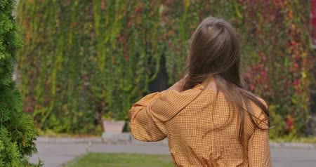 crows feet : Back view of a young Caucasian girl in mustard dress with goose foot print. Elegant woman touching her long brown hair. Cinema 4k footage ProRes HQ.