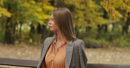 mustard : Profile portrait of an elegant Caucasian woman sitting on the bench in the park and smiling. Charming girl in checkered jacket and mustard dress spending time outdoors. Cinema 4k footage ProRes HQ.