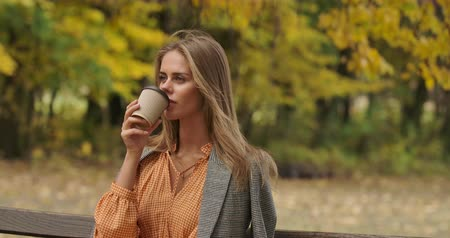 mustard : Portrait of a cute Caucasian woman sitting on the bench in the autumn park and drinking coffee. Gorgeous girl in checkered jacket and dress with goose foot having break. Cinema 4k footage ProRes HQ.