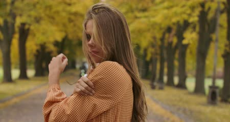 crows feet : Side view of freezed Caucasian girl with brown hair and pleasant smile standing on road in autumn park. Pretty woman in mustard dress with crows feet print tucking hair. Cinema 4k footage ProRes HQ.