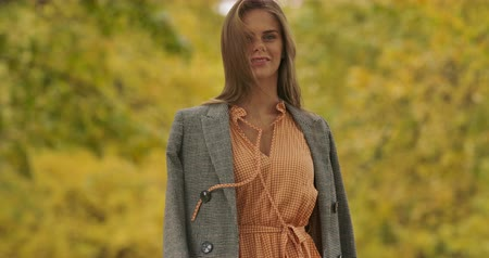 crows feet : Back view of a young Caucasian woman in checkered jacket standing in the autumn park. Charming girl turning to the camera and smiling. Cinema 4k footage ProRes HQ.