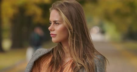 hardal : Profile portrait of beautiful Caucasian woman standing in autumn park and smiling. Charming girl in checkered jacket and mustard dress turning to camera and tucking hair. Cinema 4k footage ProRes HQ.